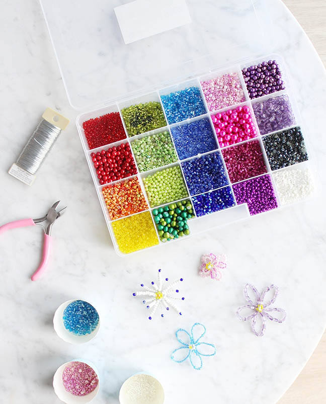 A colorful bead kit with beading tools and completed beaded flowers